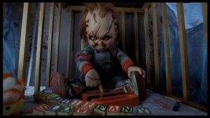 Dans sa prison de parc à bébés, Chucky s'occupe comme il peut.