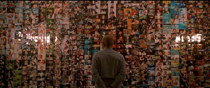 photo obsession sy face à son mur d appartement tapissé de photos de clients