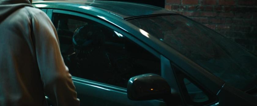 venom eddie voyant le reflet du symbiote dans une vitre de voiture