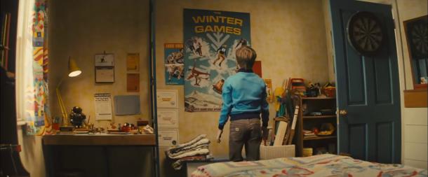 Eddie the eagle enfant devant un poster des jeux olympiques d'hiver