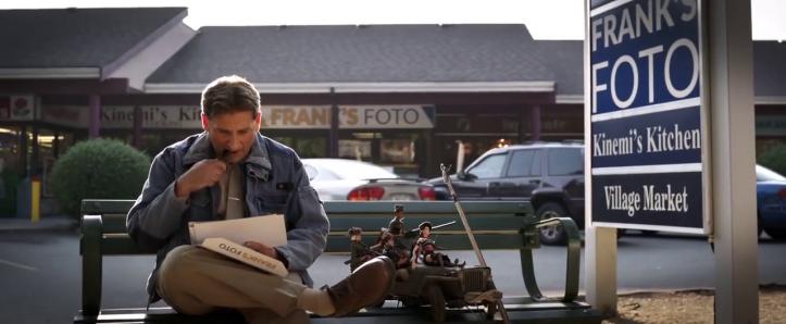 bienvenue à marwen mark assit sur un banc à cote de ses figurines