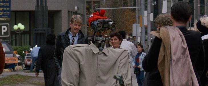 Appelez moi Johnny 5 le robot johnny 5 vetu d'un impermeable et d'un bonnet tente de se fondre parmi les humains dans les rues de new york