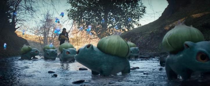 Détective pikachu film Tim tient pikachu dans ses bras et traverse une rivière en compagnie des bulbizarres et des spordodo
