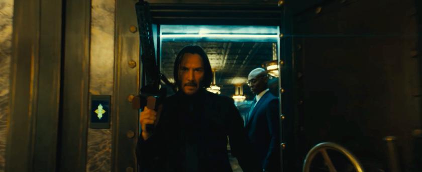 John Wick parabellum john sort armé de l'ascenseur de l'hotel continental aux cotés du concierge