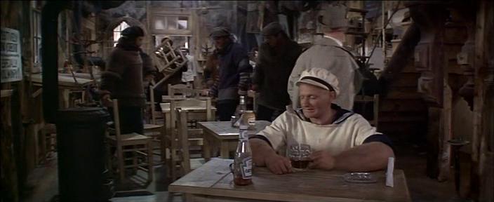 Popeye le film au bar assis à une table à boire un verre