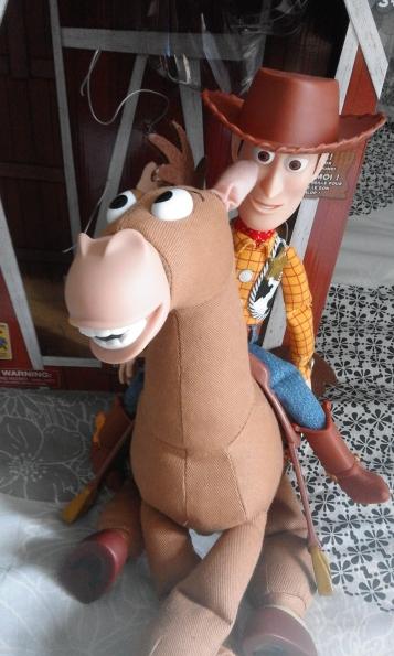 Toy Story Figurine Woody assis sur une figurine de pile poil avec à l'arrière la boite du personnage