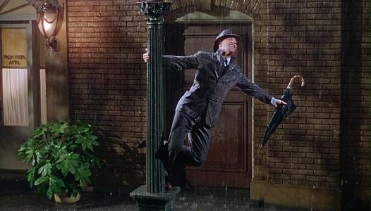 Chantons sous la pluie don lockwood se tenant à un lampadaire chante sous la pluie