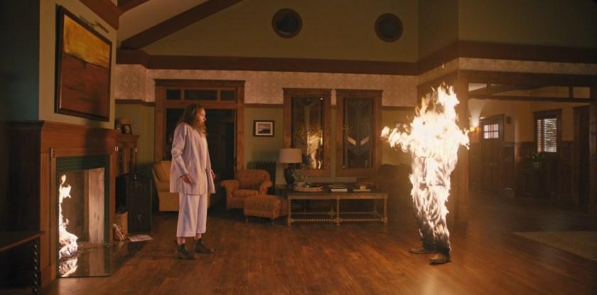 Hérédité film 2018 Annie sous le choc devant un corps en flamme dans son salon