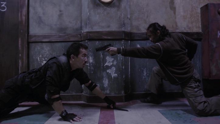 The raid Jaka à terre face à Mad Dog pointant son arme sur lui