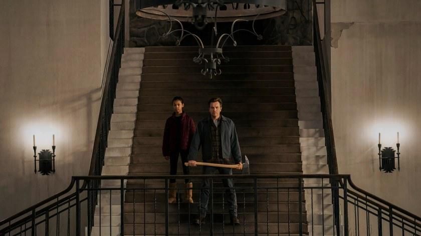 Doctor Sleep Danny armé d'une hache se tenant à coté d'Abra dans les escaliers de l'hotel Overlook
