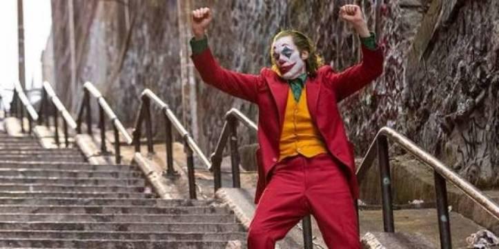 Joker 2019 Arthur en tenue de clown danse dans les escaliers