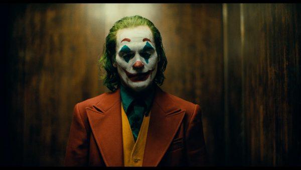 Joker 2019 Arthur maquillé en clown souri dans son ascenseur