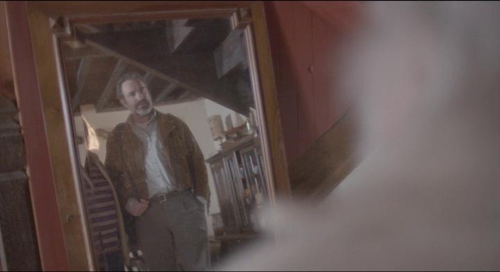 Le Daim George regarde sa veste en daim dans un miroir