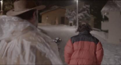 Le Daim George suit de nuit sous la neige un homme portant une doudoune