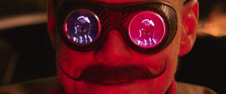 Sonic-2020-un-homme-à-moustache-voit-dans-le-reflet-de-ses-lunettes-un-hérisson-bleu-ciblé