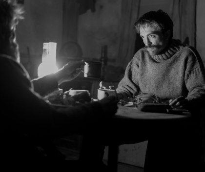 the lighthouse film un homme moustachu et un homme barbu partagent un repas