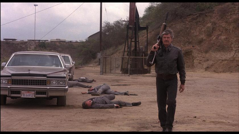 death-wish-4-the-cracksown-le-justicier-braque-les-dealers-un-homme-moustachu-fusil-à-la-main-marchant-près-de-mafieux-tués