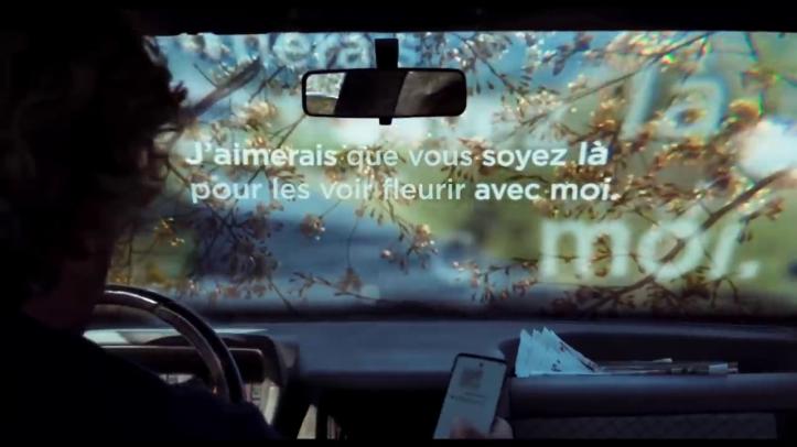 #JeSuisLà-des-mots-aparaissent-sur-le-pare-brise-de-l'intérieur-d'une-voiture