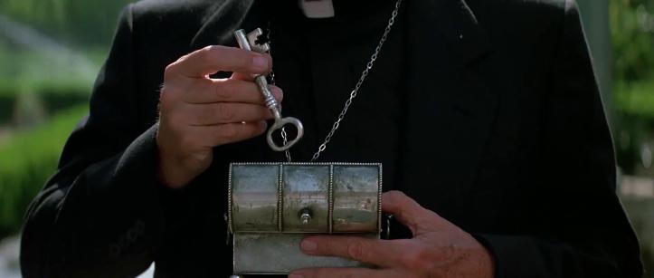 Le-prince-des-ténèbres-un-prêtre-sortant-une-clé-d'une-boite-métallique