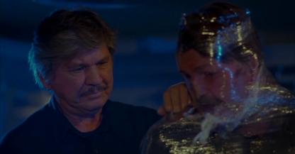 Le_Justicier_L_Ultime_Combat-un-homme-moustachu-regarde-un-homme-ficelé-dans-du-film-plastique