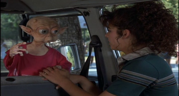 Mac-et-moi-jeune-fille-tenant-la-maib-d'un-petit-alien-portant-un-teeshirt-rouge