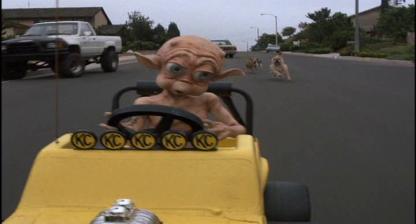 Mac-et-moi-petit-alien-dans-une-voiture-électrique-jaune-poursuivit-par-des-chiens-dans-une-ruelle