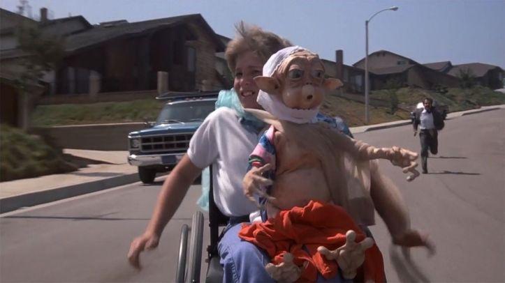 Mac_et_moi-handicapé-tenant-sur-ses-genoux-un-alien-et-poursuivi-par-des-hommes-en-costume