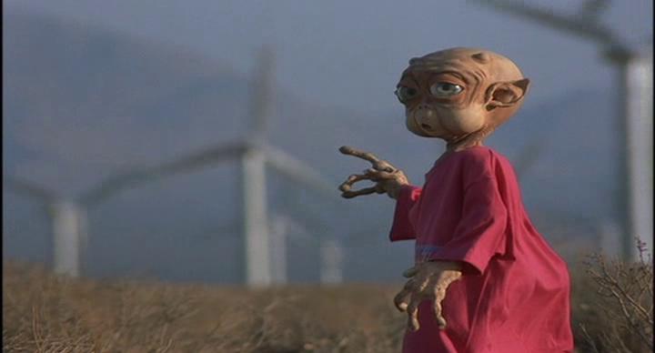 Mac_et_moi-petit-alien-portant-un-tee-shirt-rouge-montre-du-doigt-des-éoliennes