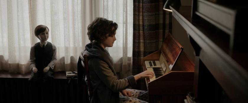 The-Boy-la-malédiction-de-Brahms-un-jeune-garçon-joue-du-piano-sous-les-ueux-de-sa-poupée