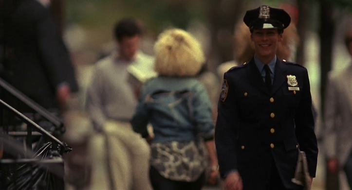 Blue-Steel-jamie-lee-curtis-en-tenue-de-policière-marche-en-souriant-dans-la-rue