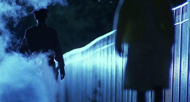 Blue-Steel-une-policière-à-la-silhouette-cachée-par-la-nuit-et-de-la-fumée-marche-dans-la-rue