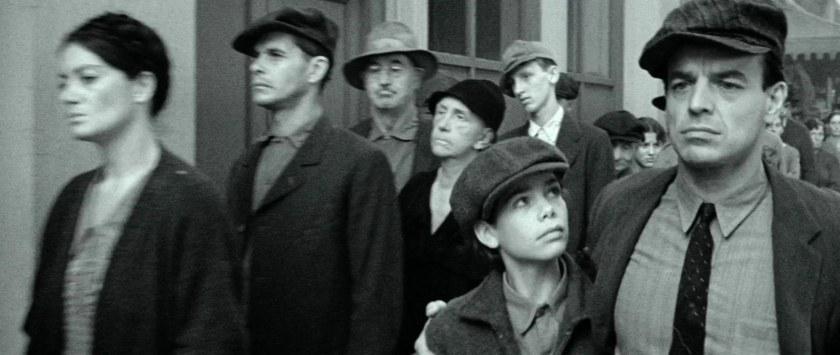natty-gann-natty-et-son-père-marchant-parmi-des-gens-tristes-photo-en-noir-et-blanc