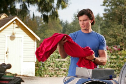 Smallville-clark-tenant-une-cape-rouge-dans-ses-bras
