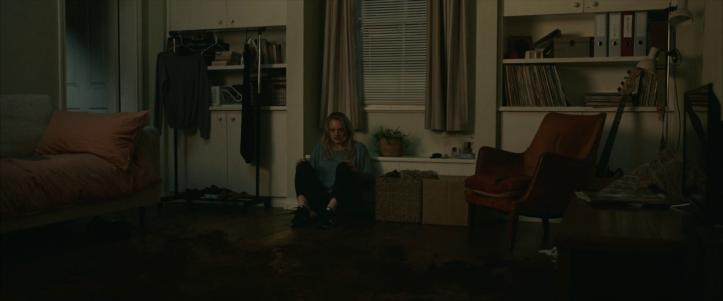 the-invisible-man-2020-femme-assise-par-terre-dans-une-chambre-fixant-quelque-chose
