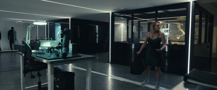 the-invisible-man-2020-femme-marchant-dans-une-pièce-d'appareils-scientifiques