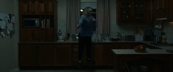 the-invisible-man-2020-femme-tenant-un-coutea-empoignée-par-une-force-invisible-dans-une-cuisine