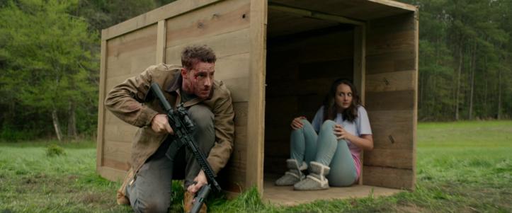 The-hunt-2020-un-homme-armé-d'un-fusil-se-met-à-couvert-contre-une-caisse-abritant-une-femme-apeurée-le-fixant