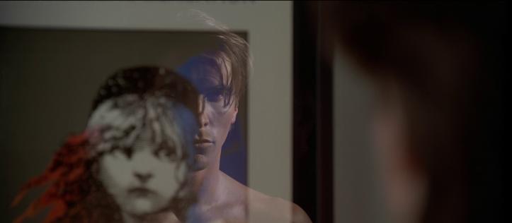american-psycho-patrick-bateman-regardant-son-reflet-dans-un-cadre-représentant-une-jeune-femme