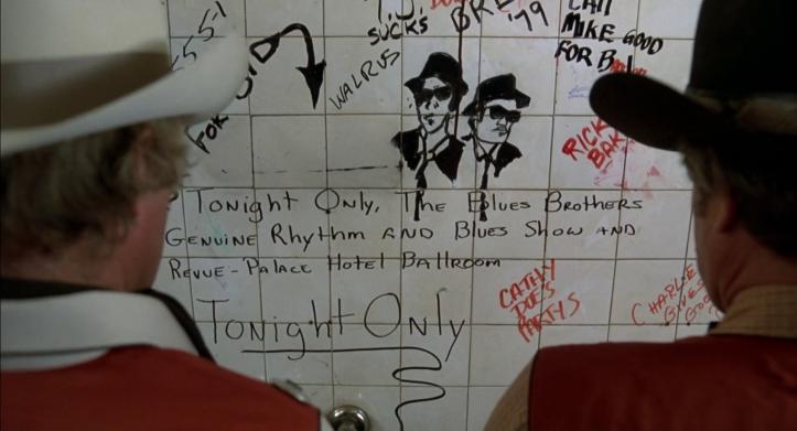 Les-Blues-Brothers-deux-texan-lisent-l'invitation-du-concert-des-blues-brothers-taguée-sur-les-murs-de-toilettes