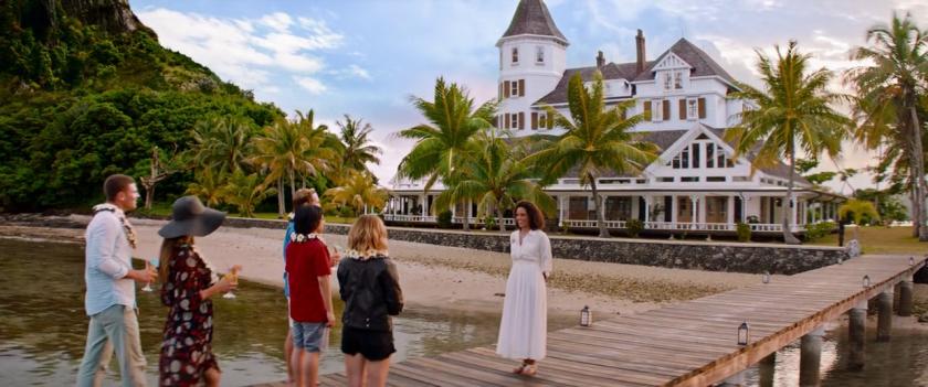 Nightmare-Island-une-hotesse-accueille-des-invités-devant-un-complexe-hotelier-situé-sur-une-ile-paradisiaque