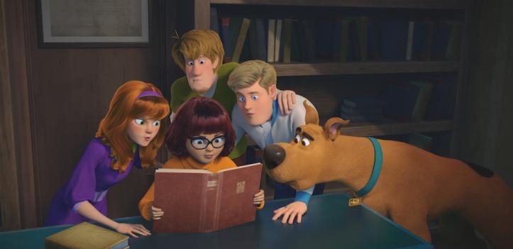 Scooby-2020-daphne-sammy-fred-et-scooby-rassemblés-autour-de-vera-lisant-un-livre
