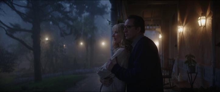 color-out-of-space-un-homme-portant-des-lunettes-prend-sa-femme-dans-ses-bras-en-regardant-la-nuit-tomber-dans-leur-ferme